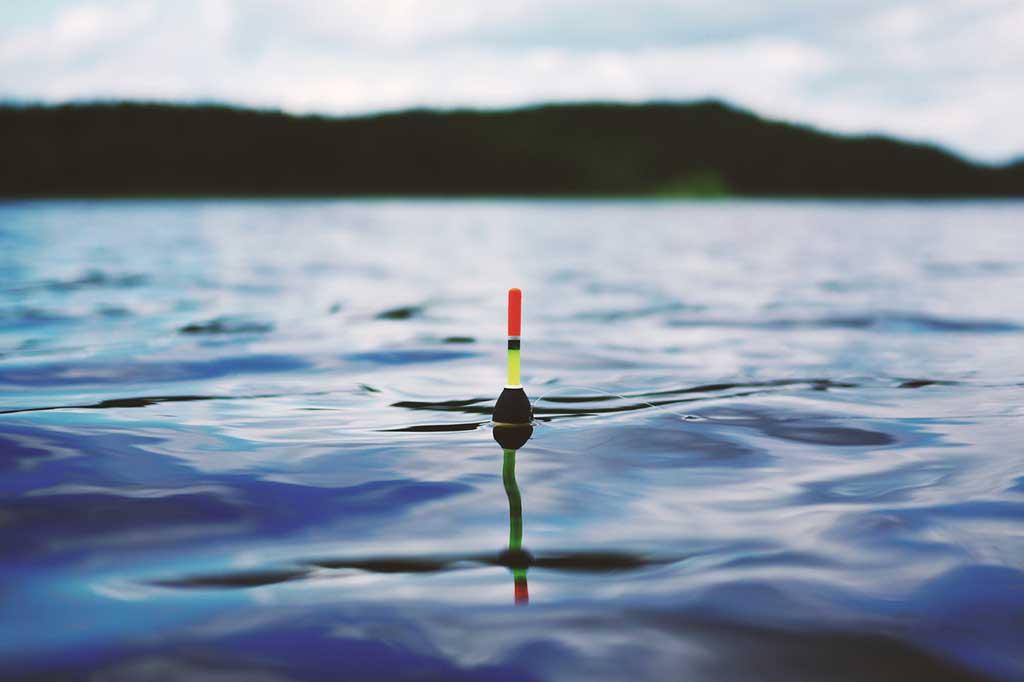 La Pesca y las tablas solunares. Imagen de Corcho de pesca sobre agua.
